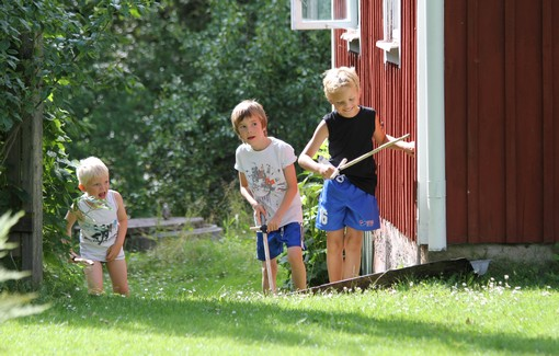 Barn smyger vid husknut med träsvärd i händerna.