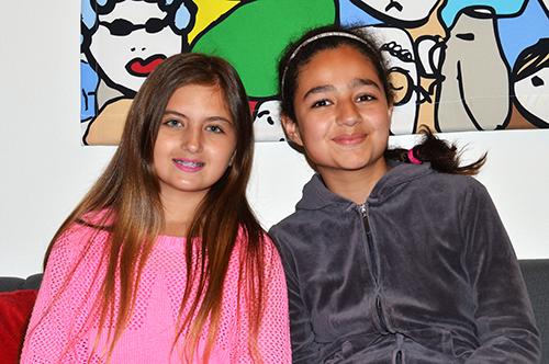 Två flickor tittar in i kameran.