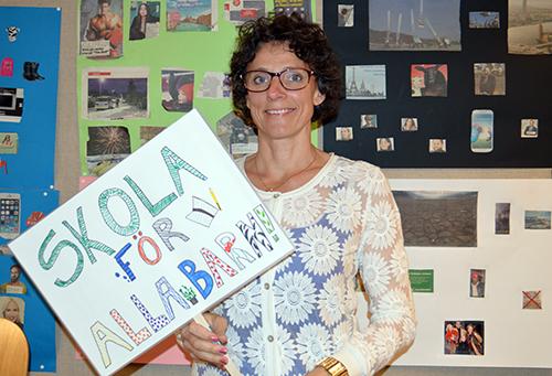 Lärare håller upp hemmagjort plakat där det står: Skola för alla barn.