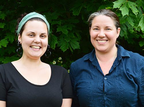 Två kvinnor står framför träd.