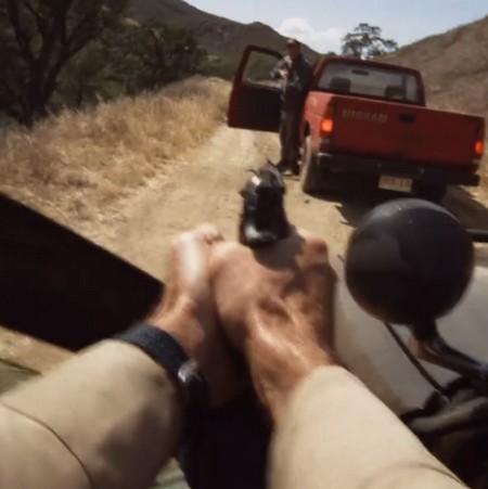 Händer som håller pistol riktas mot man i röd bil.