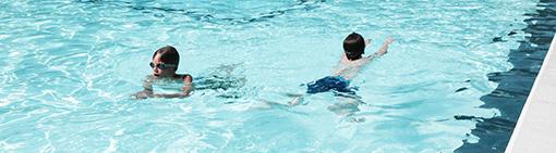 Två barn simmar i pool.