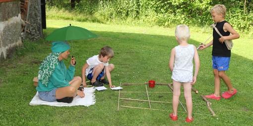 Tre barn spelar spel på gräsmattan samtidigt som en vuxen sitter med dem under ett grönt paraply.