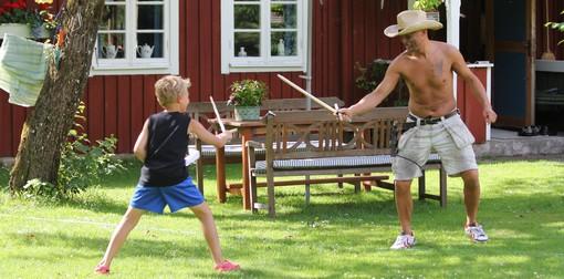 Barn och man leker med träsvärd.