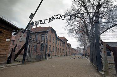 """Ingång till Auschwitz med skylten """"Arbeit macht frei""""."""
