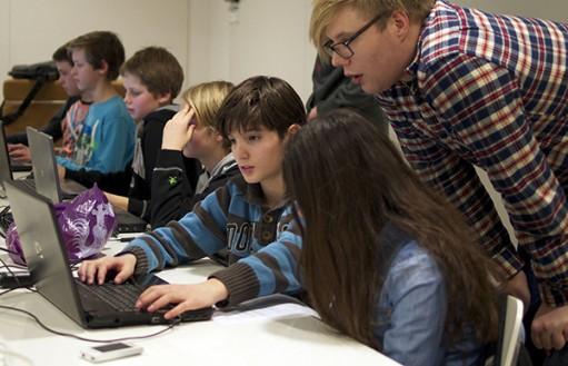 Elever lutar sig fram mot dator.
