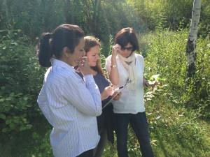 Tre kvinnor tittar på papper fäst på skrivbräda.