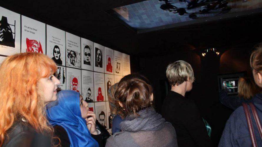 Texter uppsatta på vägg i svart kub.