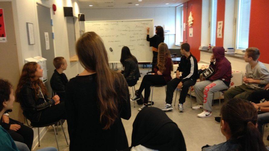 Elever sitter i ring medan kvinna skriver på whiteboard.