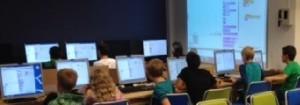 Elever sitter på rad framför datorer.