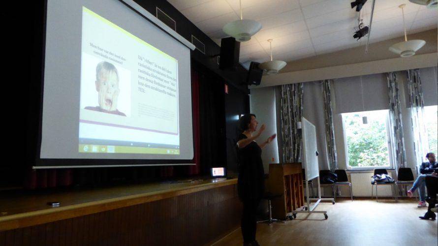 Kvinna föreläser framför projicerad presentation.