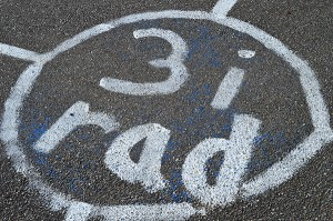 Rund vit cirkel på asfalt där det står tre i rad.