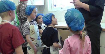 Barn med blå platsmössor i kök.