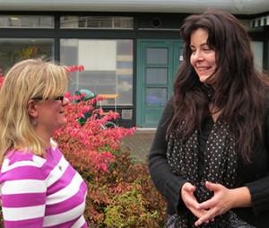 Två kvinnor pratar med varandra utomhus.