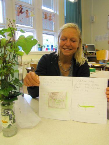 Kvinna visar upp saga som elev skrivit.