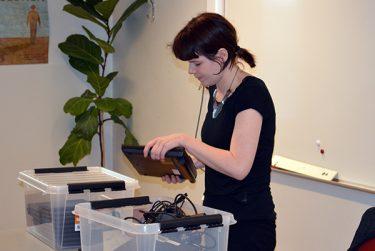 Kvinna plockar fram teknik ur lådor.