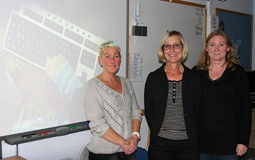 Tre kvinnor föreläser framför projicerad presentation.