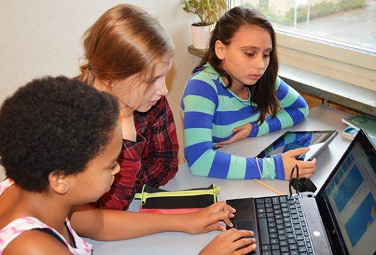 Tre elever tittar in i dator.