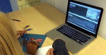 Elever redigerar film på dator.