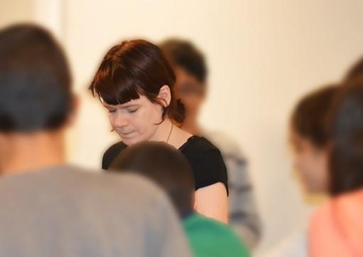 Kvinna hjälper elever.