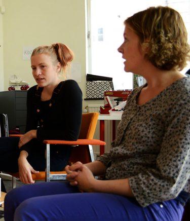 Två kvinnor sitter och samtalar.