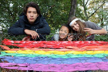 Barn framför stängsel där de har vävt in regnbågsflaggan.