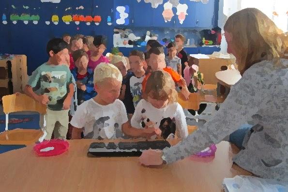 Barn tränar på att trycka på tangentbord som pedagog håller fram.