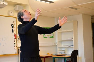 Pedagog slår ut händerna.