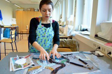 Kvinna gör konstverk med pärlor.