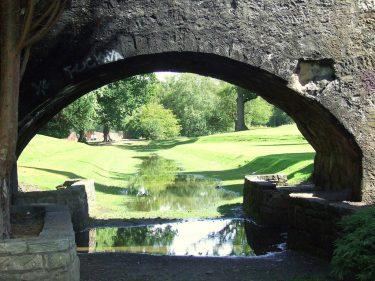 Stenbro med grön å som flyter under.