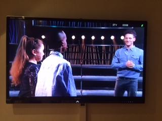 TV som visar programledare och två barn.