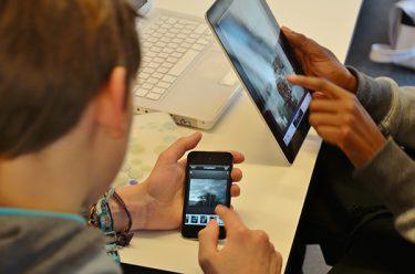 Barn trycker på ipad och mobilskärm.