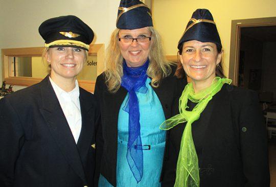 Tre kvinnor med flygkaptenshatt.