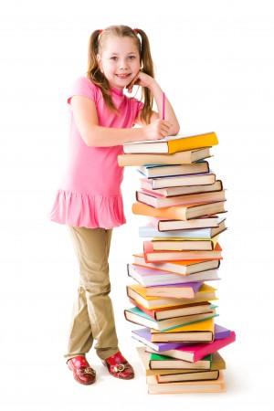 Flicka lutar sig mot hög av böcker.