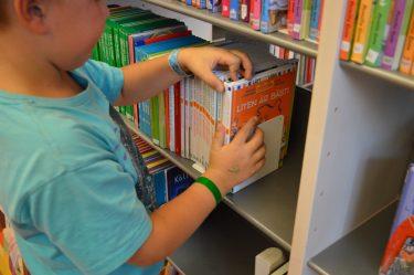 Pojke letar igenom böcker i hylla.
