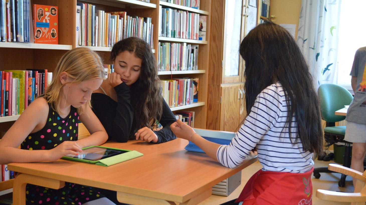 Elever sitter vid bord och jobbar med en ipad.