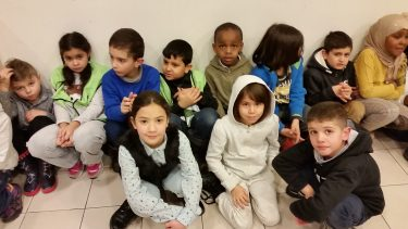 Elever på golvet i kapprum.