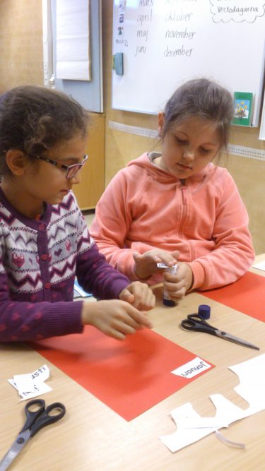 Elever sitter och jobbar vid bord.