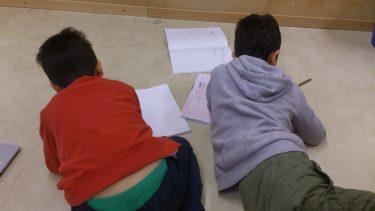 Elever sitter på golvet och skriver.