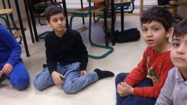 Elever sitter på golvet och pratar.