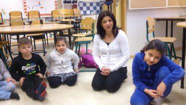 Kvinna och barn sitter på golvet i klassrum.