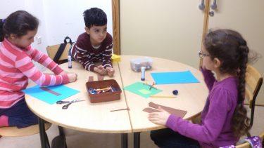 Tre barn pysslar vid bord.