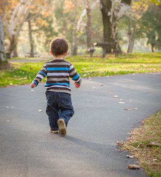 Barn går iväg på asfaltväg.