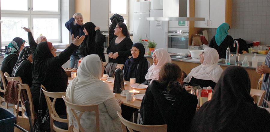 Kvinnor i kök klädda i förkläden och kvinnor som sitter runt bord.