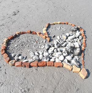 Hjärta format av stenar på strand.