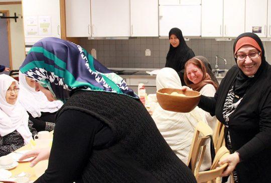 Kvinnor i kök klädda i förkläden.