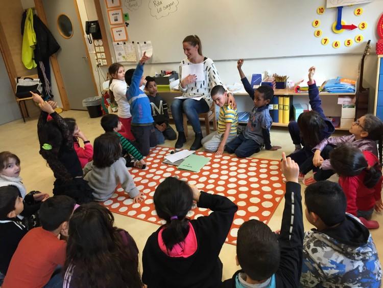 Lärare läser för barngrupp som sitter på golvet.