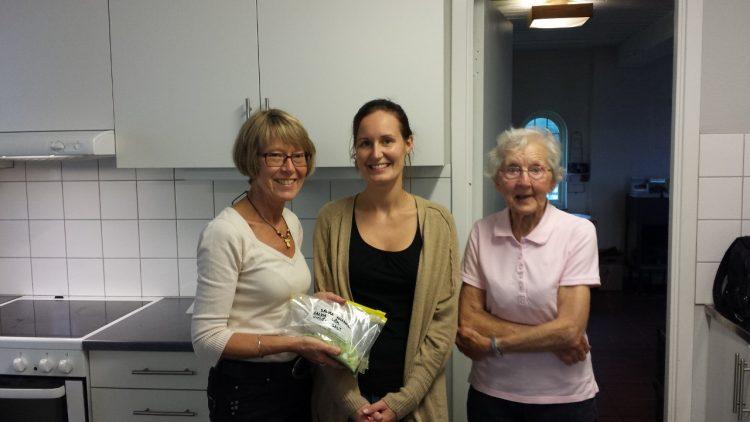 Tre kvinnor står i ett kök.