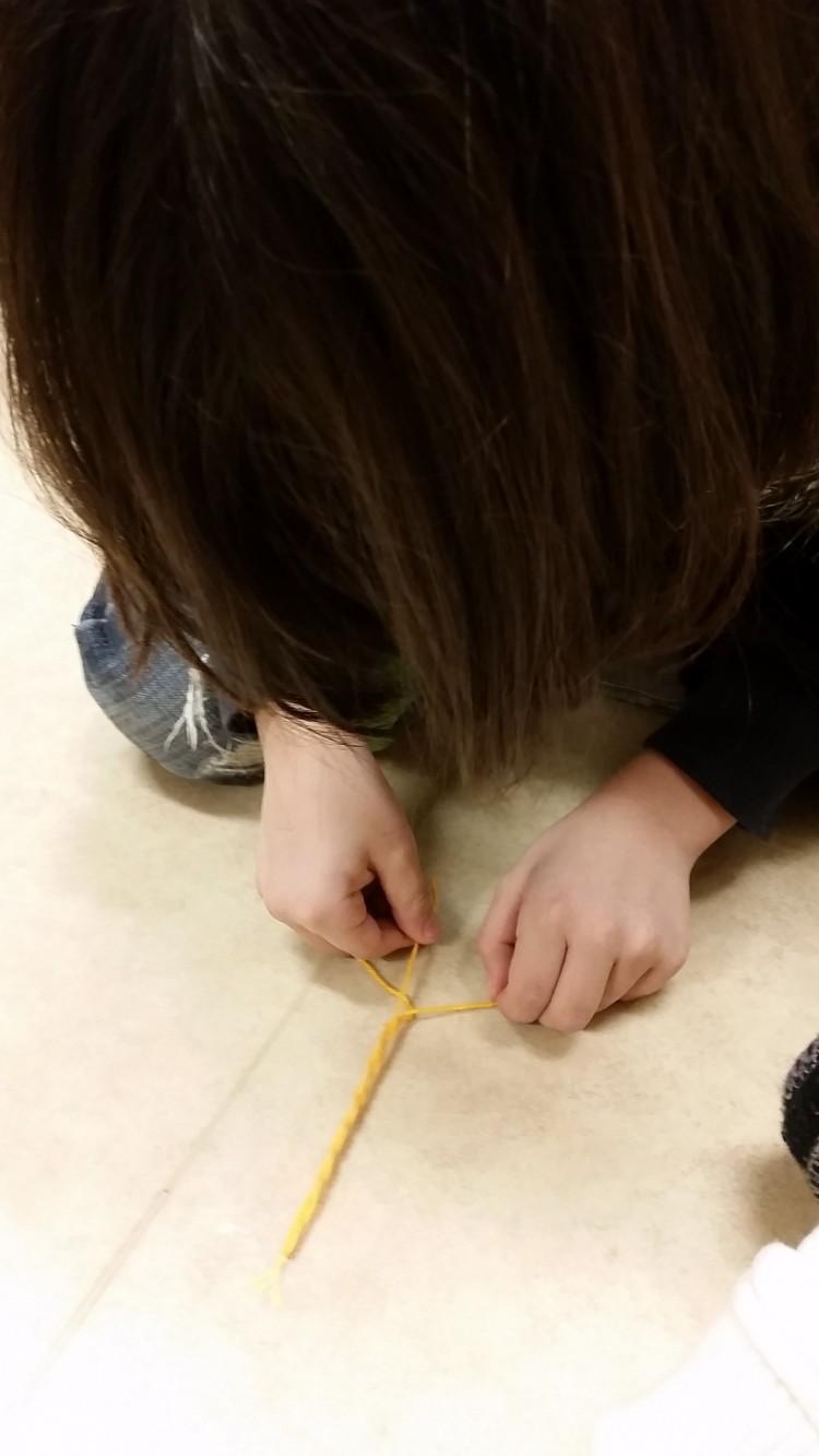 Barn tejpar gul tofs på golvet.
