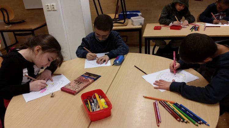 Tre barn sitter och ritar.
